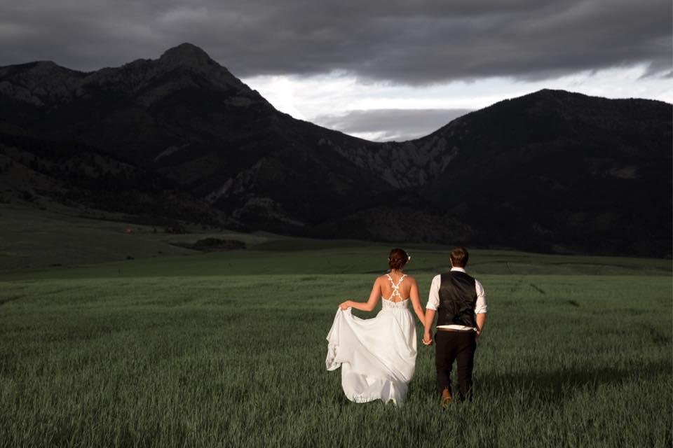 bride and groom against montana mountains