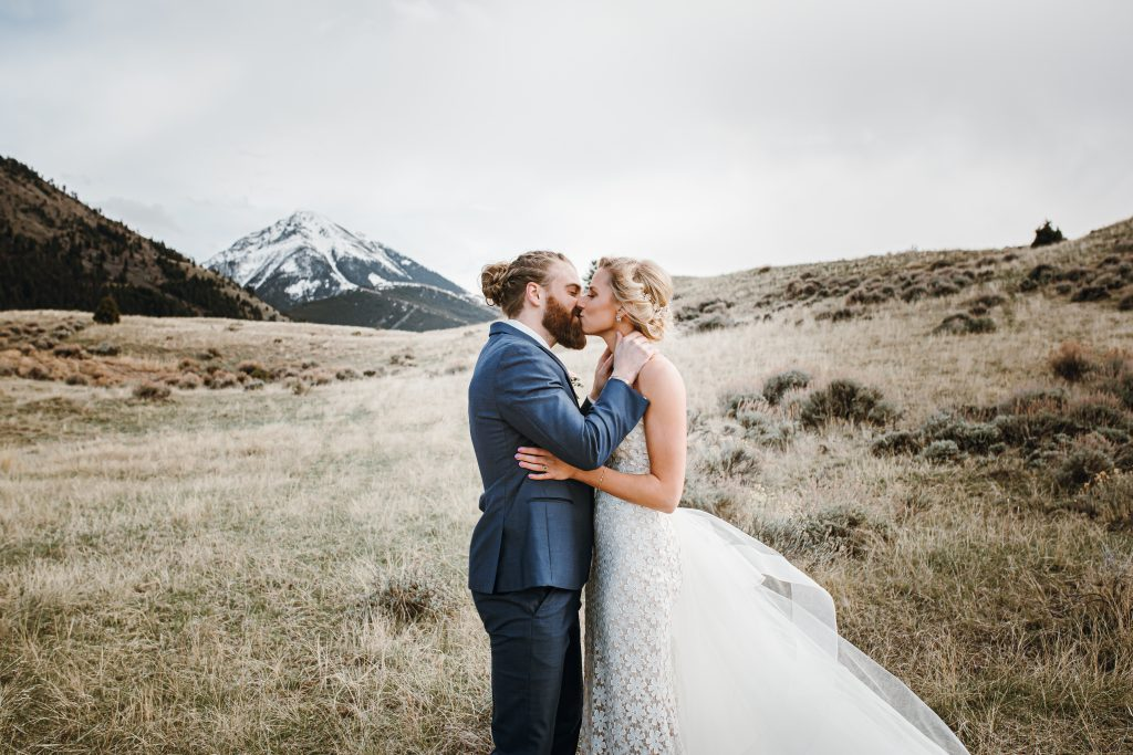 bride and groom kissing with mountains in the background