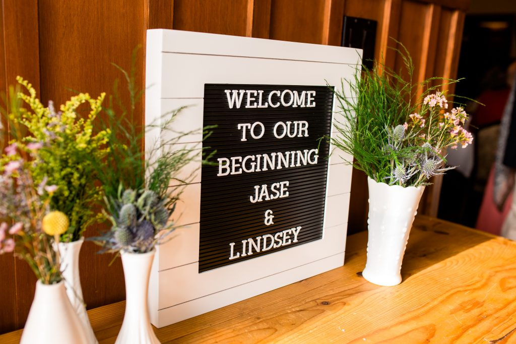 letter board used as the welcome sign with flowers around it