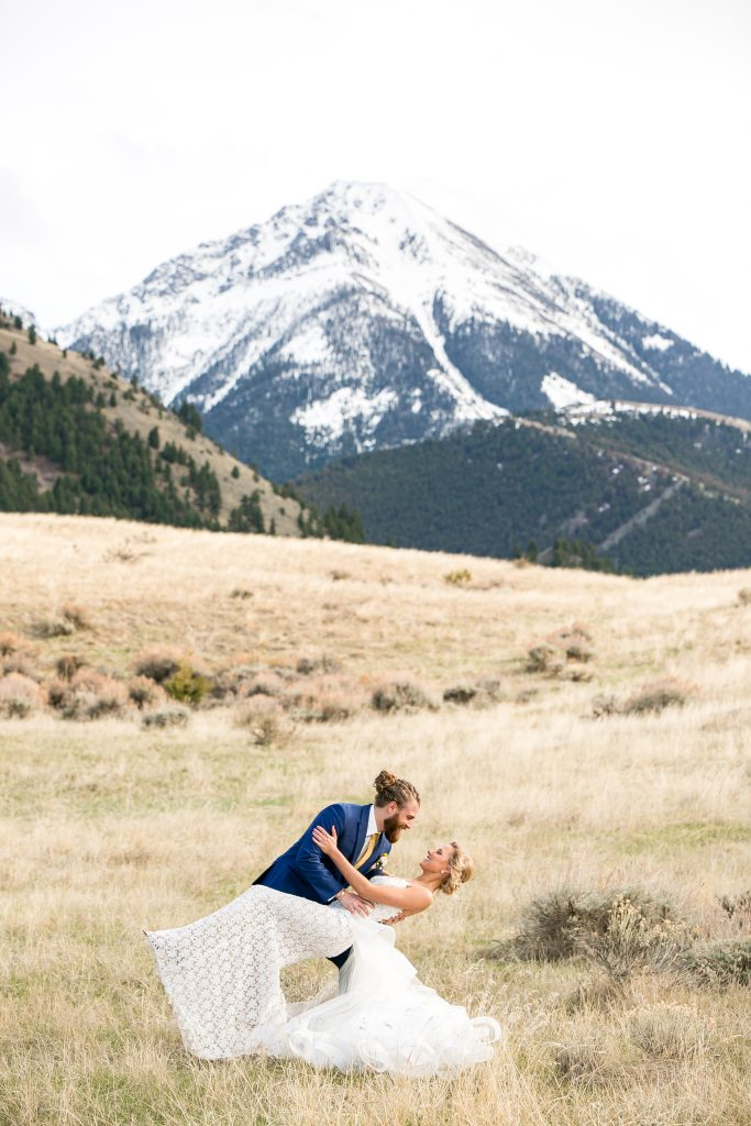 groom dipping the bride with mountains in the background