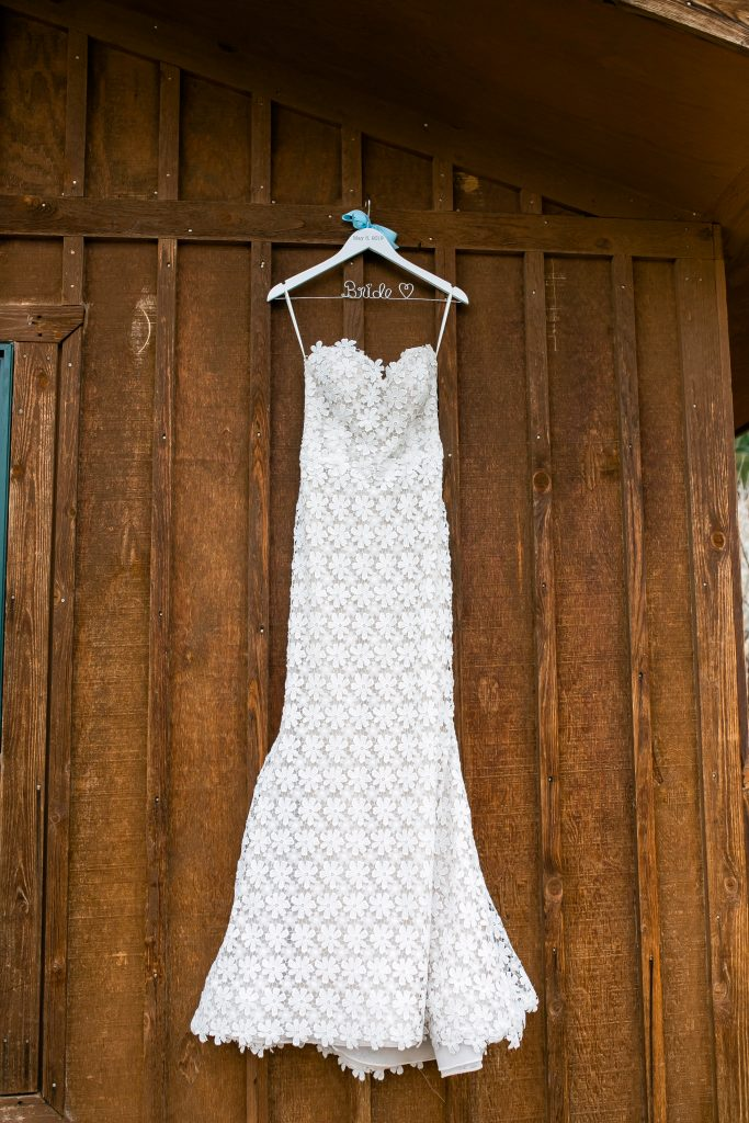 brides wedding dress hanging against a wood building
