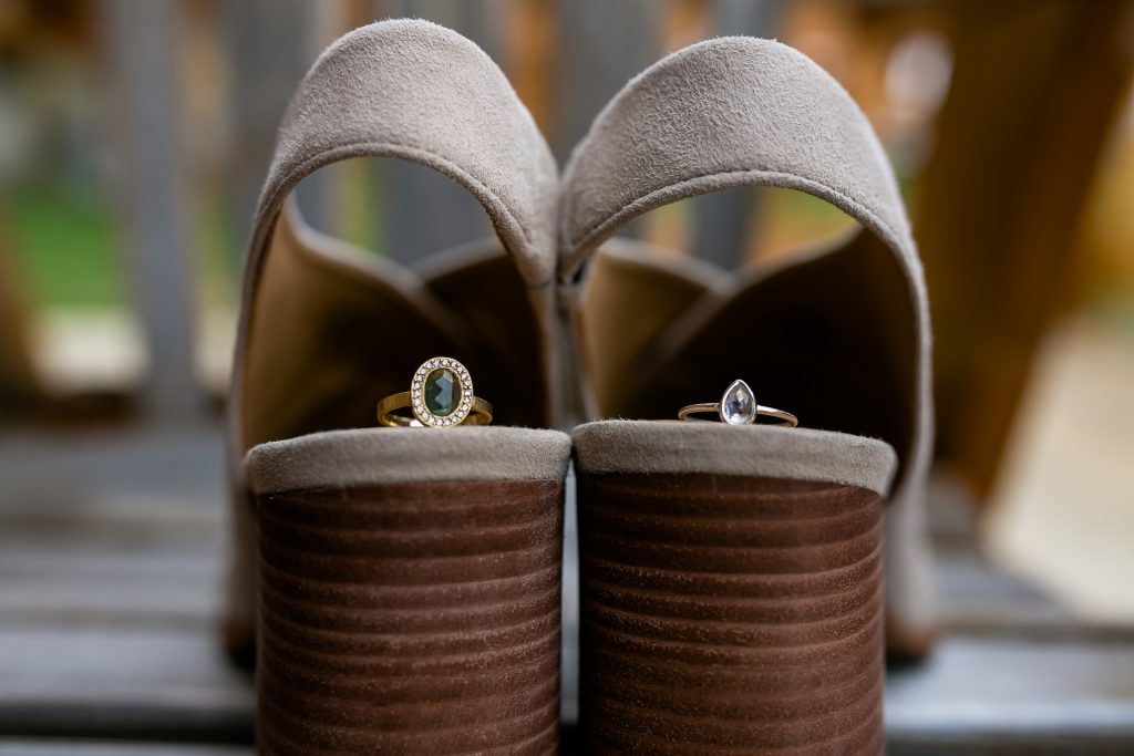 brides shoes with her engagement ring and wedding ring on them
