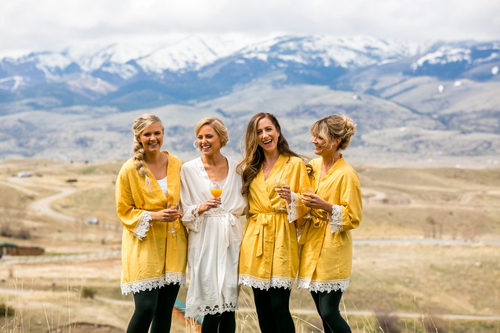 bride and bridesmaids standing outside with mountains in the background