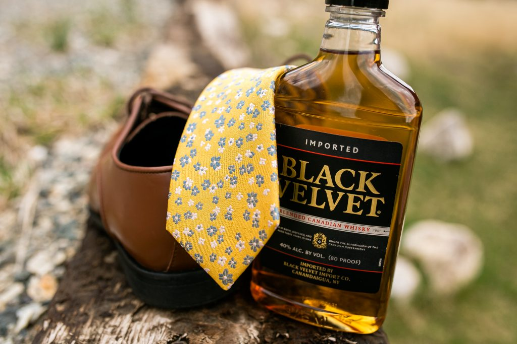 Grooms tie laid over his shoes with a bottle of black velvet