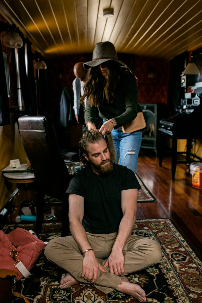groom sitting on the floor getting his hair braided
