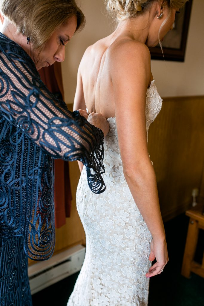 brides mom buttoning up the back of her dress