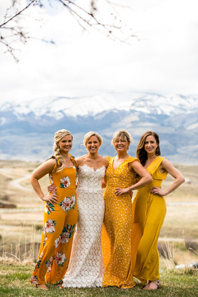 bride and her bridesmaids in their dresses with mountains in the background