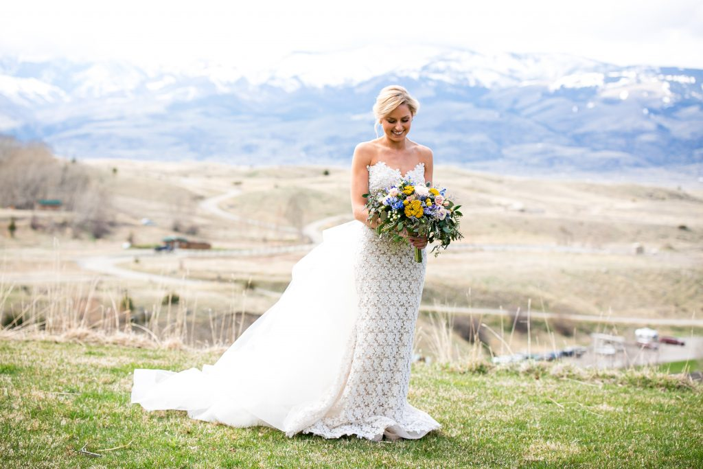bride in her dress looking down at her flowers with mountains in the background