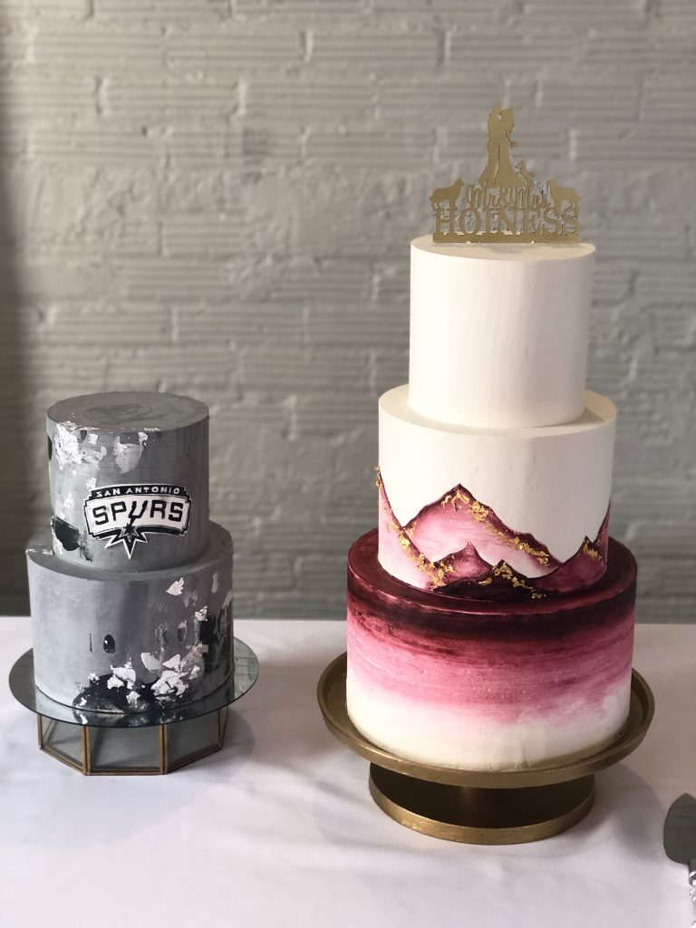 wedding cake with mountains on it and a grooms cake with the Spurs logo on it