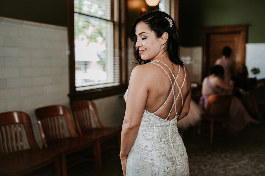 Bride in her wedding dress looking over her shoulder