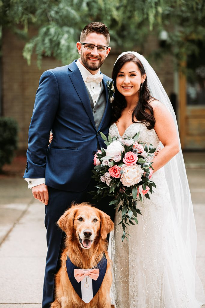 bride and groom with their dog standing outside