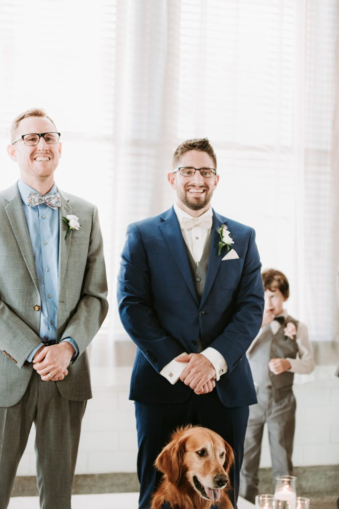 Groom and officiant watching the bride walk down the aisle
