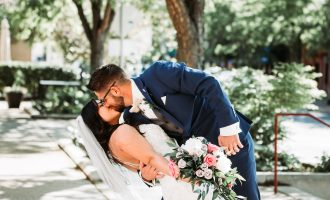 groom dipping bride and kissing her outside of the Billings Depot