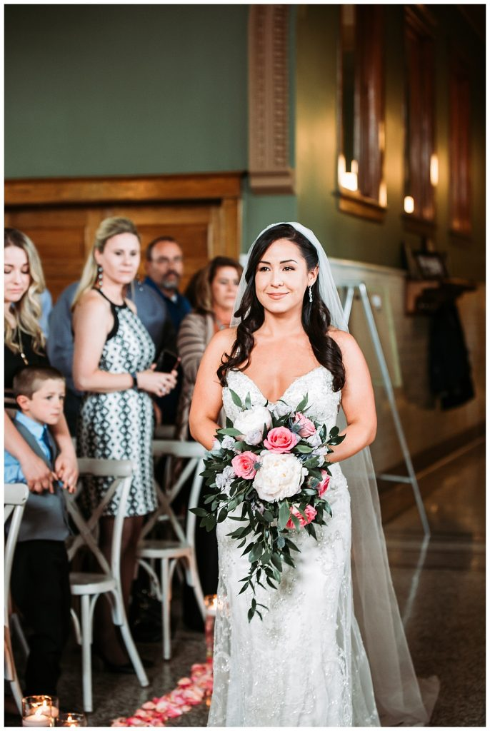 bride holding her flowers walking down the aisle in the Billings Depot