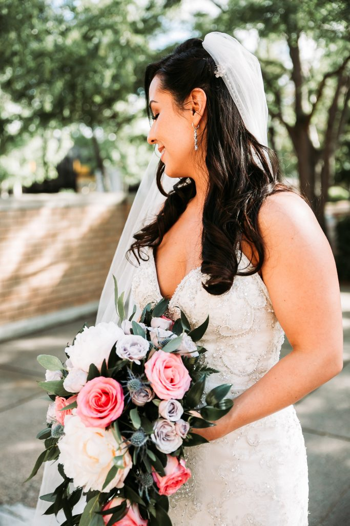 bride in her wedding dress holding flowers looking over her shoulder