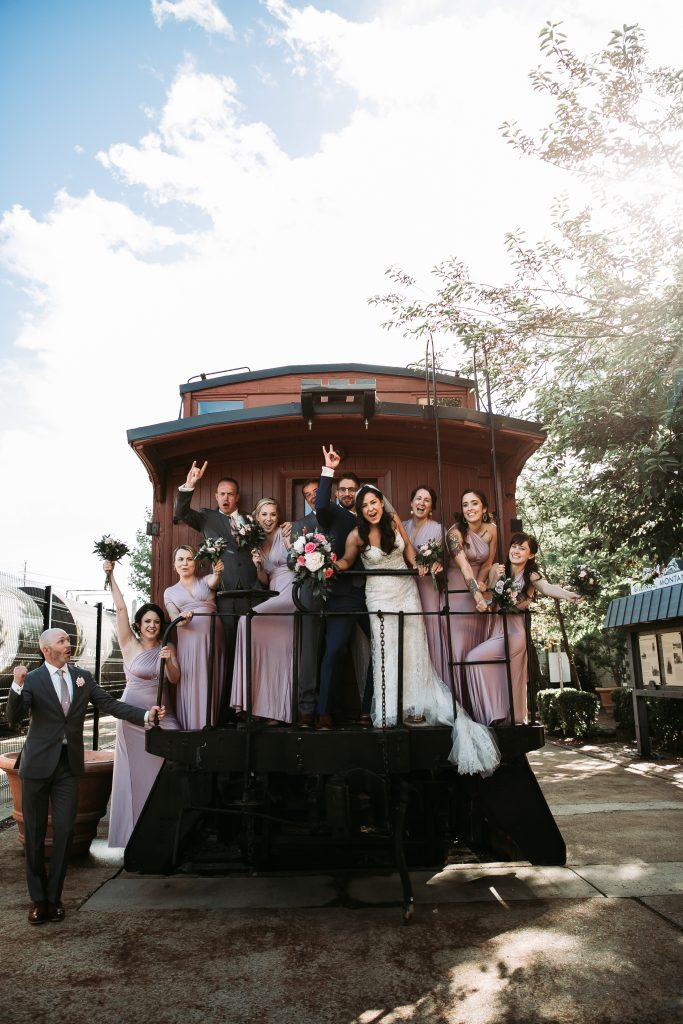 whole wedding party cheering for bride and groom on the back of a train car