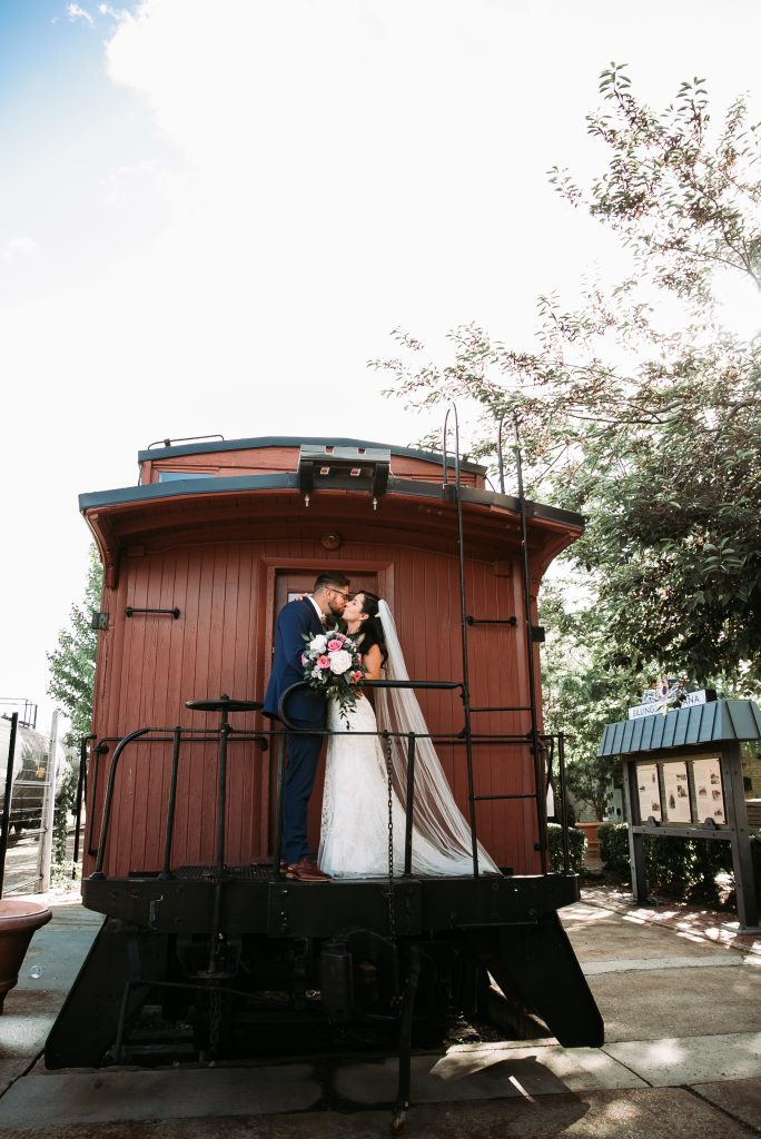 bride and groom kissing on the back of a train at the Billings Depot