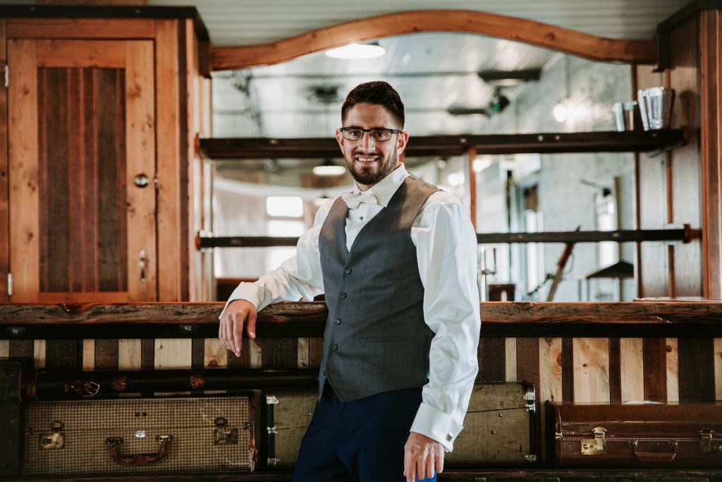 groom in his suite leaning against bar at the Billings Depot