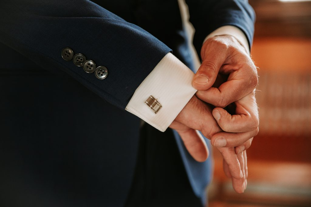 grooms hands adjusting the sleeves of his jacket