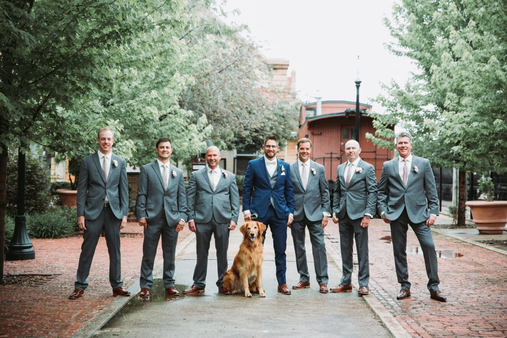 groom in a blue suite and groomsmen in grey suites standing in a line