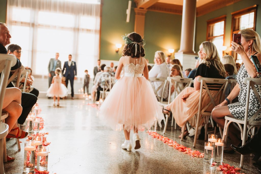 flower girls in pink dresses walking down the aisle at the Billings Depot