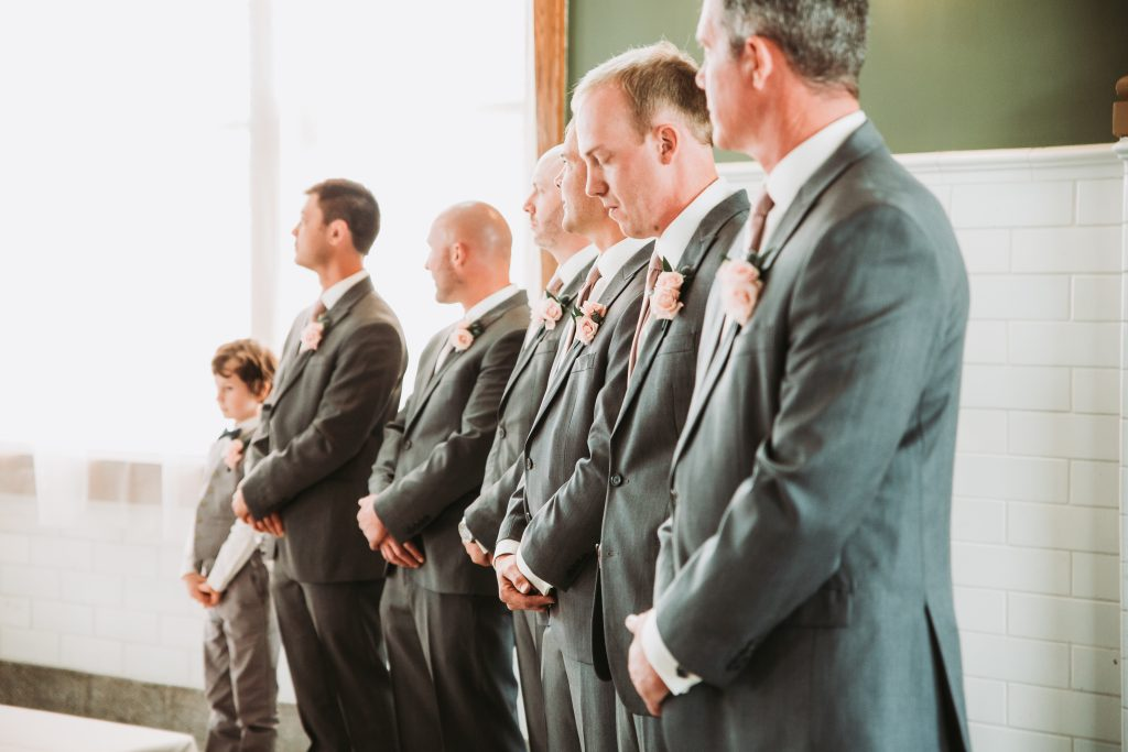 groomsmen in grey suits standing together during ceremony