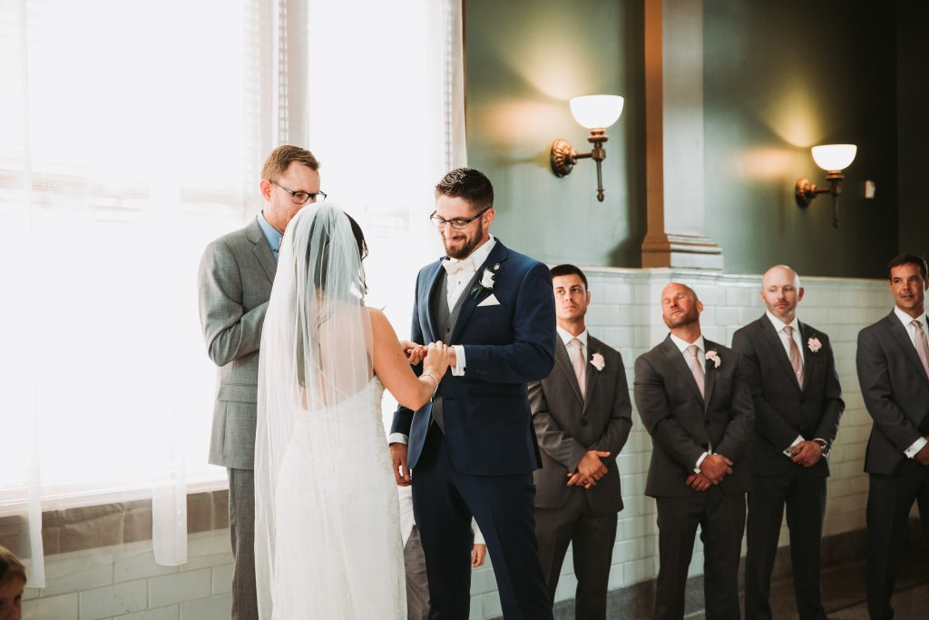 bride and groom holding hands during ceremony with groomsmen in the background