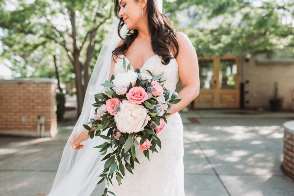 bride holding her flowers standing outside of the Billings Depot