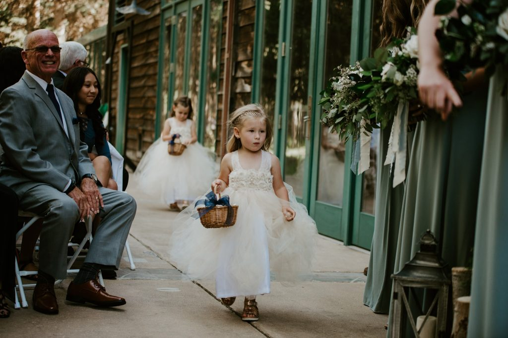 flower girls walking down the aisle at Rock Creek Resort