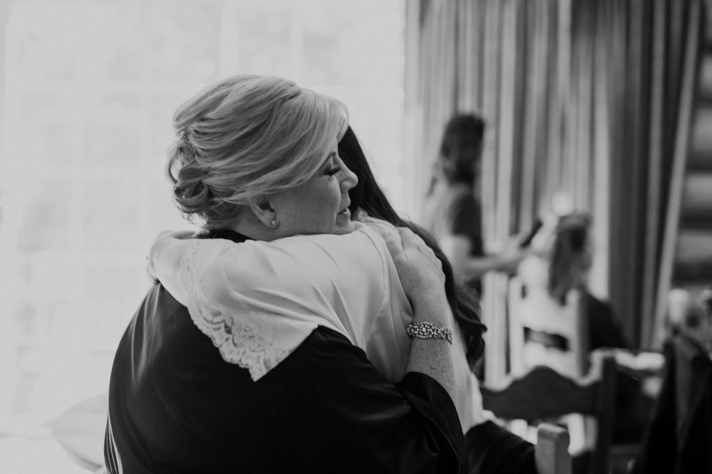 bride and mom hugging each other while getting ready