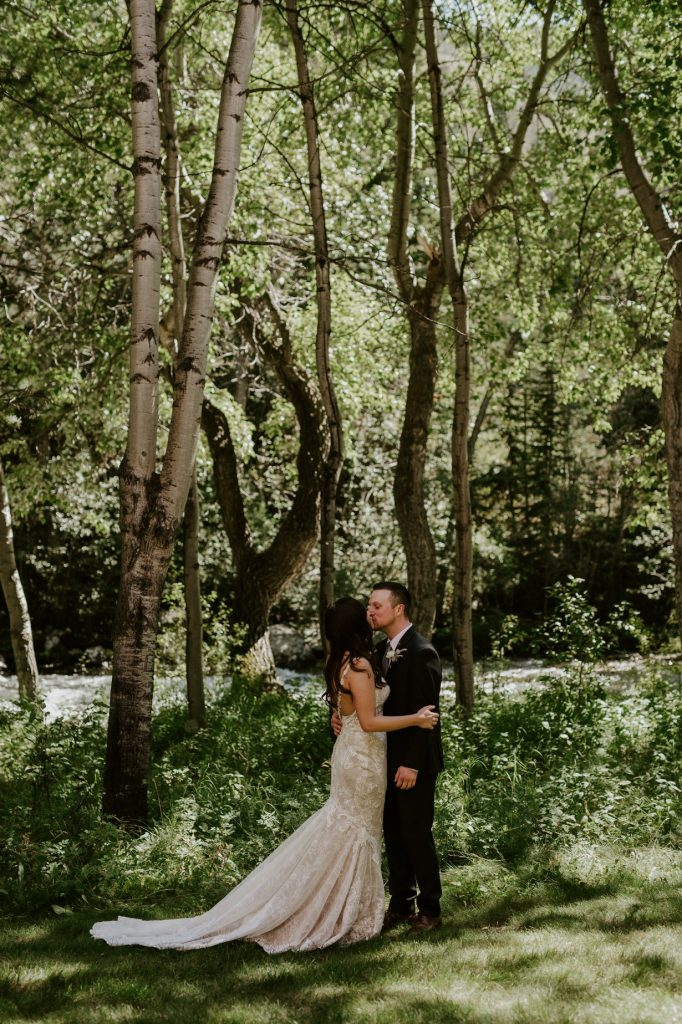 bride and groom kissing with trees and river in the background