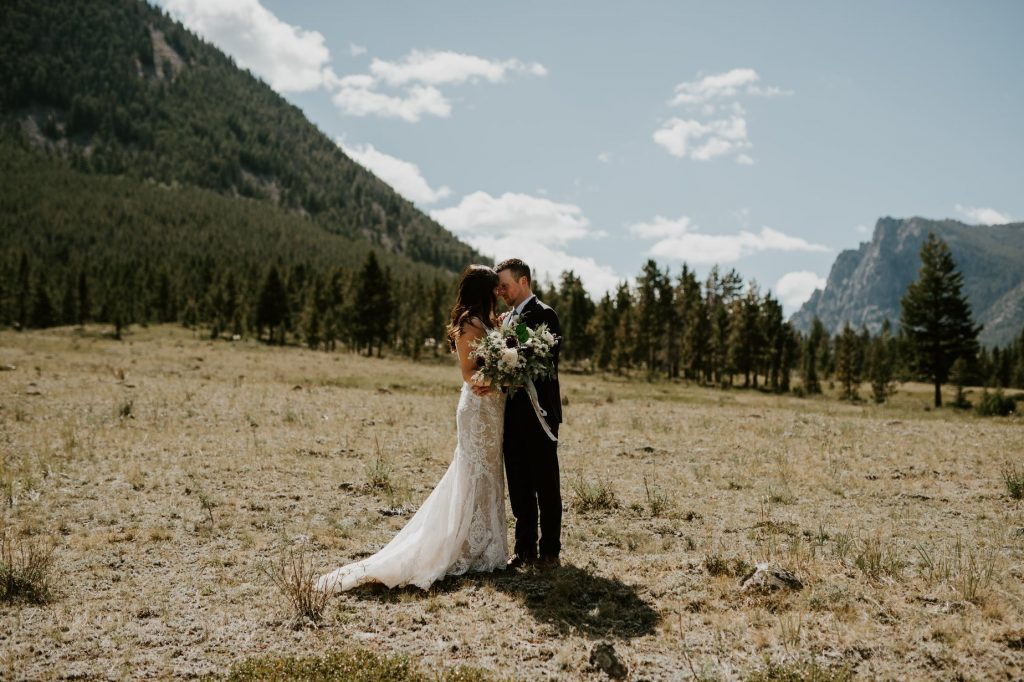 bride and groom kissing with Red Lodge Montana mountains in the background
