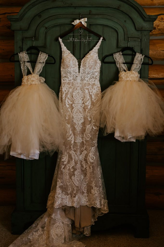 brides dress hanging up with flower girl dresses on each side