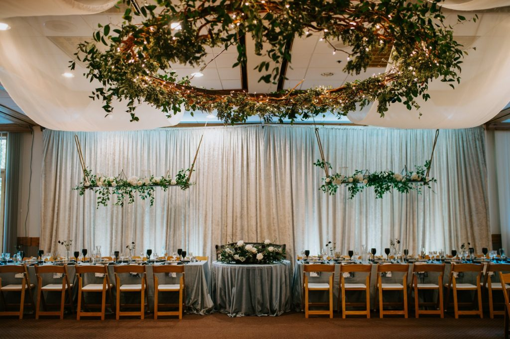 wedding reception head table with greenery suspended from the ceiling