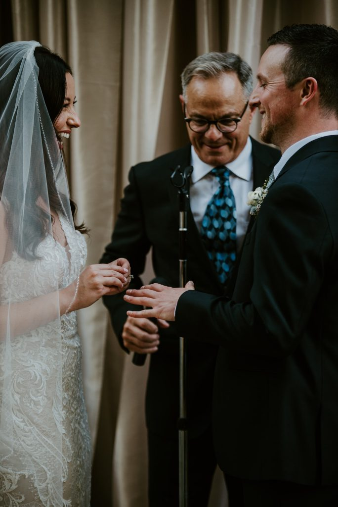 bride placing the grooms ring on his finger