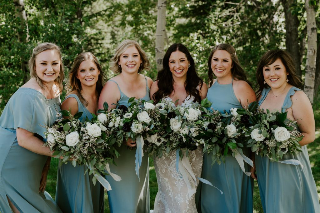 bride with her bridesmaids standing together with trees in the background