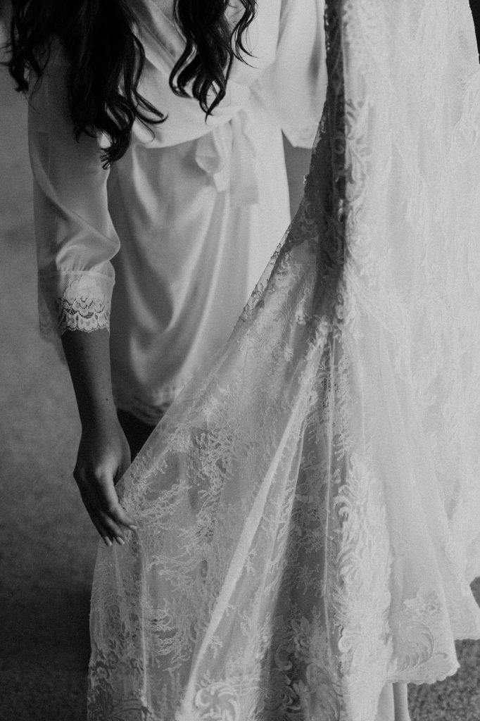 black and white picture of the bride holding her dress