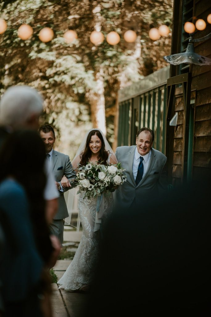 bride walking down the aisle with her Dad and Step Dad