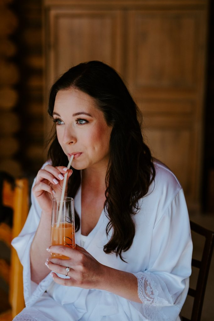 bride drinking wine while sitting in her robe