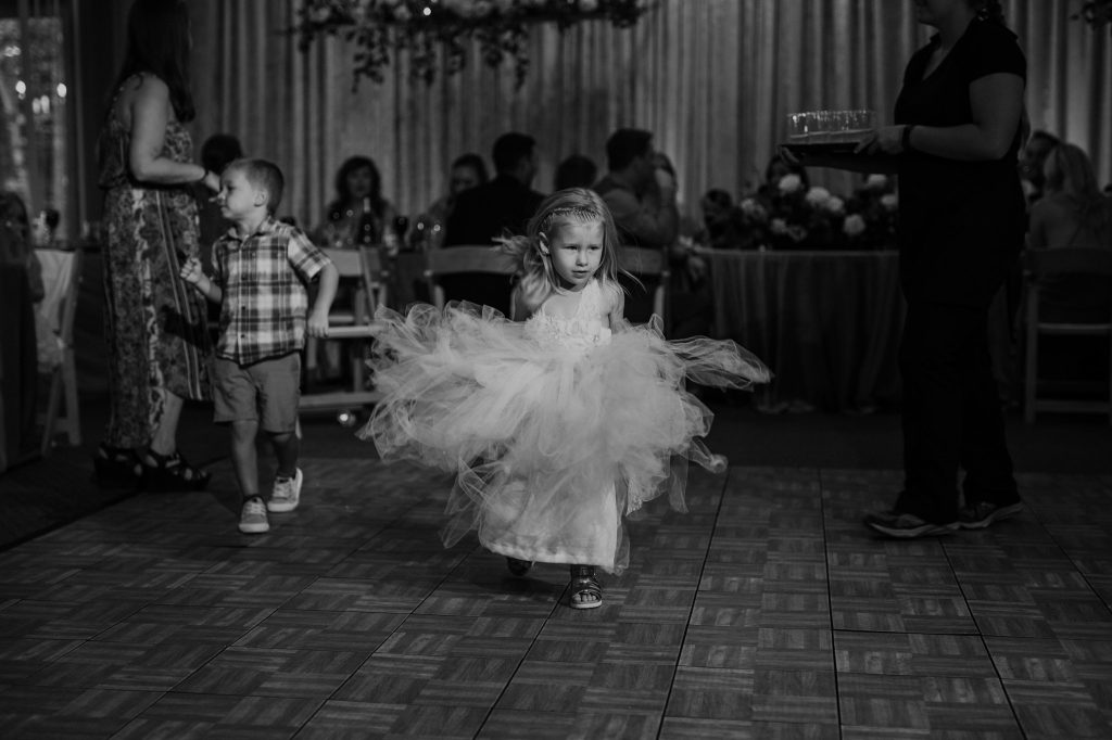flower girl twirling her dress around dancing