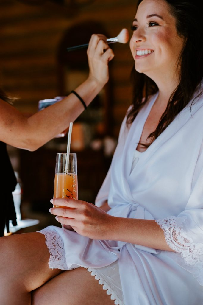 bride getting her makeup done while drinking some wine