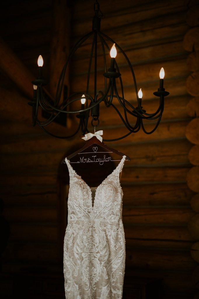 brides wedding dress hanging from chandelier
