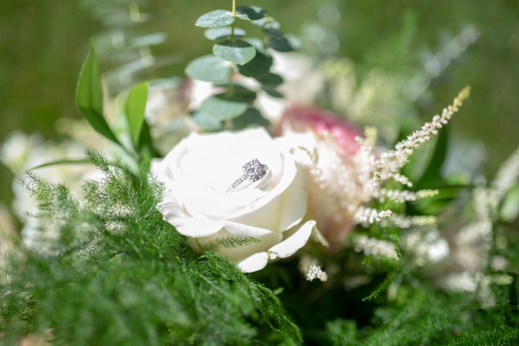 brides wedding ring sitting in her flowers