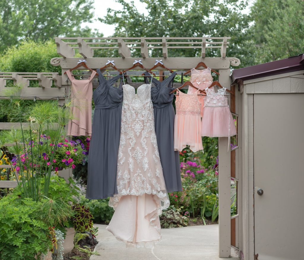 brides dress hanging up with the bridesmaids and flower girls