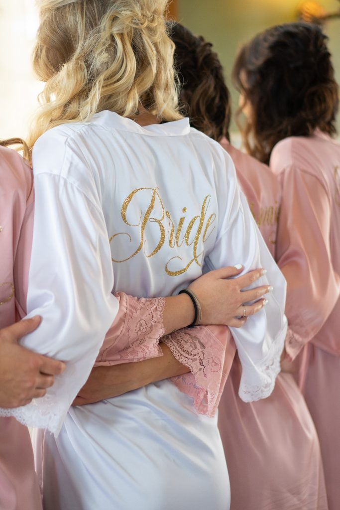 bride wearing while robe with bride written on the back