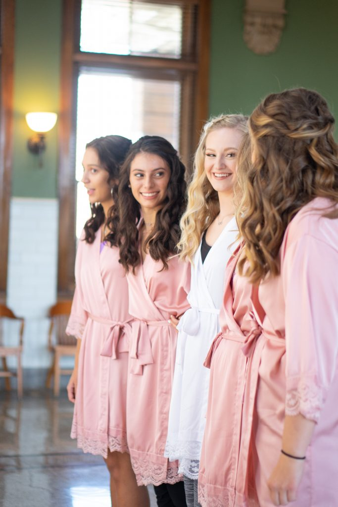 bridesmaids in their matching pink robes and the bride in a white robe