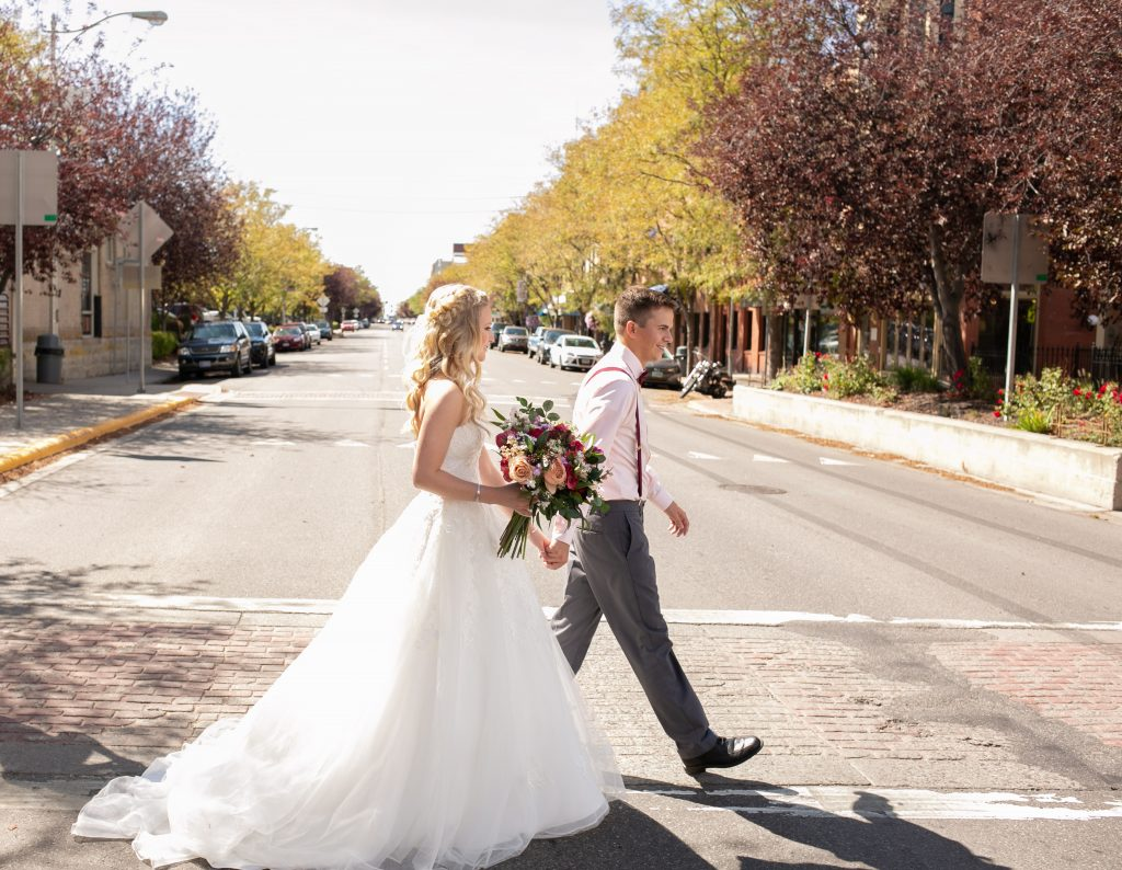 bride and groom walking across the street