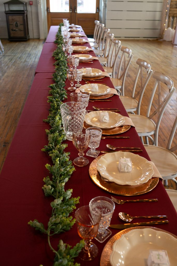 head table with place settings and greenery