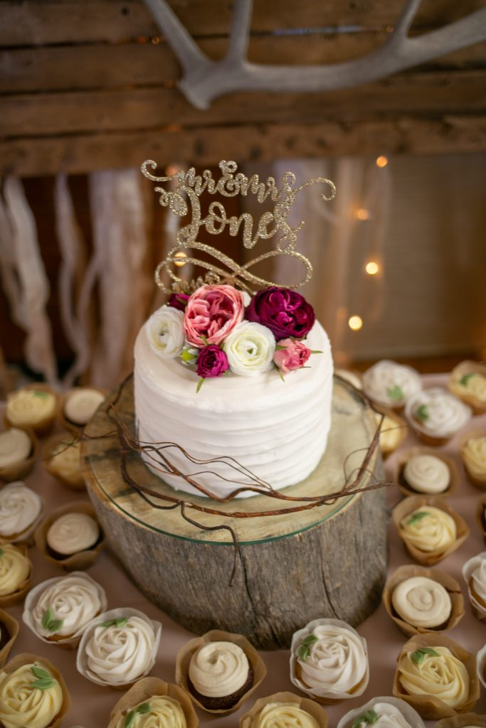 wedding cake on a wooden stand and flowers on the top