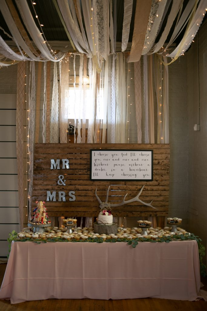 cake table with wooden sign behind it